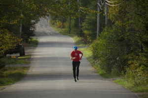 man in red shirt running on paved road