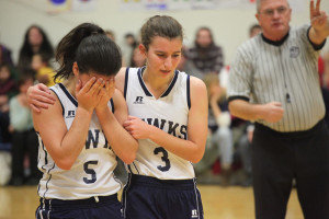 girl basketball player with her face in her hands, teammate tries to comfort her