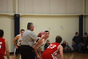 basketball referee about to throw up the ball to begin game