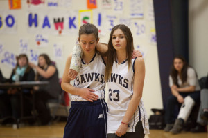 two girl basketball players, one in a cast with her arm around the other